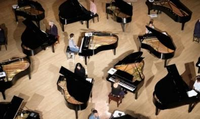 Una fotografía cenital de una sala llena de pianos y pianistas