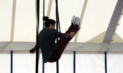 Un artista fa equilibris en un trapezi durant la representació