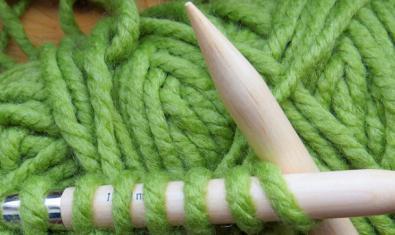 Fotografía de primer plan de unas agujas de tricotar y una prenda de ropa a medio tejer
