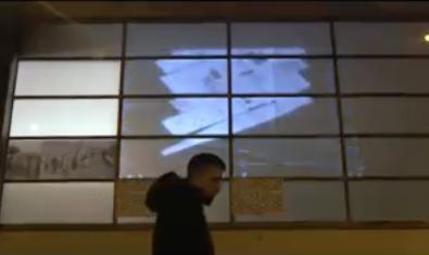 Una imatge d'un dels vídeos que s'han elaborat per presentar el projecte amb un noi passant davant d'una façana de vidre
