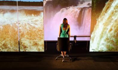 La Claudia d'esquenes a la càmera mirant les imatges d'uns paisatges de l'Argentina.