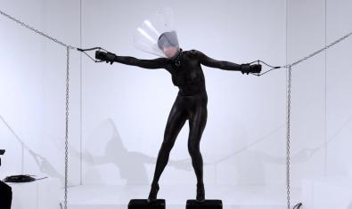 Imagen de una de las obras de Morey donde se ve un hombre vestido de negro con collar de perro y suspendido de unas cadenas