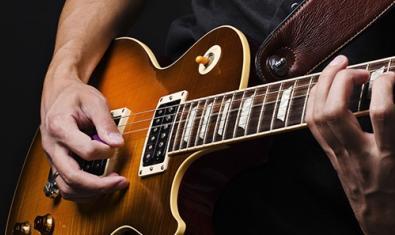 Un primer pla d'un músic tocant una guitarra serveix per promocionar la trobada