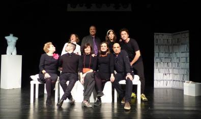 Els membres de la companyia retratats asseguts a l'escenari d'un teatre
