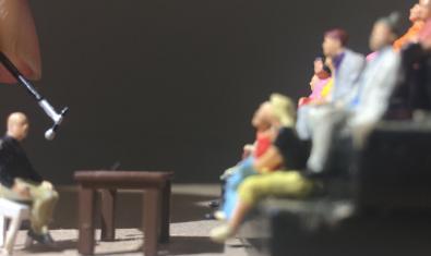 Un dedo manipula unos muñecos en miniatura que hacen las veces de espectadores