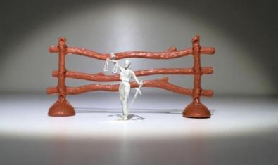 Una figureta d'una dona amb una espassa en una mà i una balança a l'altra. De fons, una tanca de troncs.