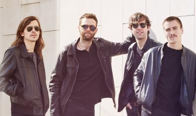 Els quatre membres de la banda fotografiats en exteriors recolzats contra un mur blanc