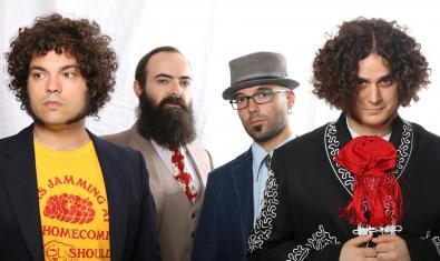 Retrato de grupo de los cuatro integrantes de la banda vistiendo sombreros, lazos rojos y unas grandes barbas
