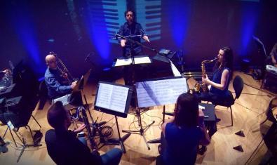 Els membres de la formació col·locats en cercle durant la interpretació d'una peça musical