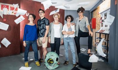 Els actors i actrius de la companyia retratats entre un munt de papers que volen per l'aire