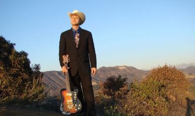 El artista con sombrero de cowboy retratado con su guitarra en un paisaje del oeste americano