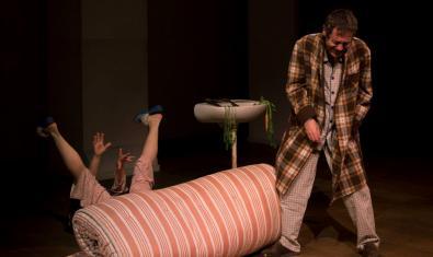 Un home en pijama i bata d'estar per casa i una dona embolicada en un matalàs en un moment de la representació