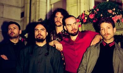 Retrato de grupo de los cinco integrantes de la banda a la entrada de un edificio