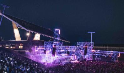 Una imagen de uno de los escenarios principales del acontecimiento iluminado durante la noche y rodeado de público