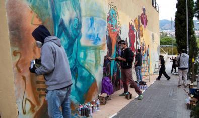 Un grupo de jóvenes hace un grafiti de forma colectiva