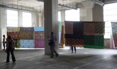 Una fotografía de un gran espacio industrial vacío con unas telas colgadas en el interior
