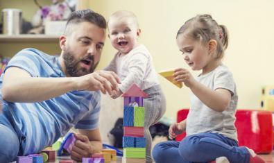 Fotografía de un padre con dos niños jugando con piezas de construcción