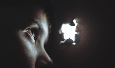 Un nen mira a través d'un forat