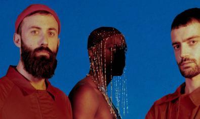 Retrat dels tres components de la banda, dos amb camises vermelles i un tercer amb una mena de vel que li cobreix el rostre