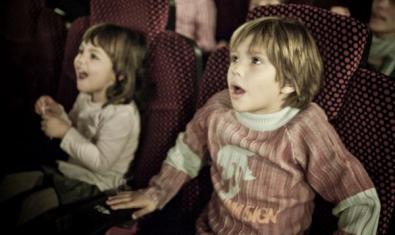 Dos nens amb cara de sorpresa asseguts als seients del cinema.