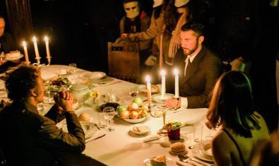 Los actores sentados alrededor de una mesa y rodeados de personajes enmascarados en uno de los montajes que forman parte de la muestra