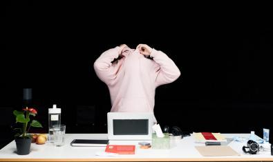 Una performer traient-se un jersei de color blanc davant d'una taula d'escriptori en un moment de la representació