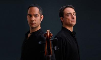 Els dos músics tocant-se l'esquena l'un amb l'altre i el violoncel a primera línia entre tots dos.