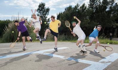 Els integrants de la formació fent un salt amb raquetes a la mà mentre fan veure que juguen al tennis