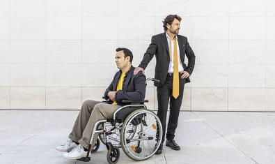 Los dos protagonistas del espectáculo uno de pie y el otro a su lado sentado en una silla de ruedas