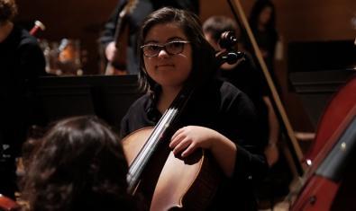 Retrato de una de las intérpretes de la orquesta con su instrumento
