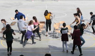 Un grup de nois i noies de l'Institut Viladomat distribueixen un seguit de cadires per la superfície d'una pista esportiva