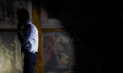 La imatge d'un visitant que es mira uns quadres en penombra il·lustra un projecte artístic centrat en el  MNAC