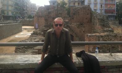 Retrato del músico Brian Pile con gafas de sol y ante unos restos arqueológicos