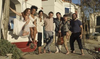 Retrat de grup dels integrants de la banda en un carrer de cases baixes