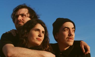 Los tres miembros de la banda barcelonesa retratados abrazándose en un espacio exterior