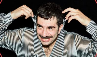 El músic vestit de ratlles agafant-se amb les mans les puntes del coll de la camisa