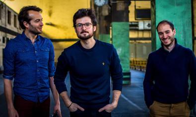 Los tres miembros de la banda retratados en el interior de un espacio fabril