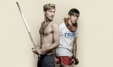 Un hombre medio desnudo con una corona y una espada en la mano y, a su lado, otro hombre con ropa deportiva.