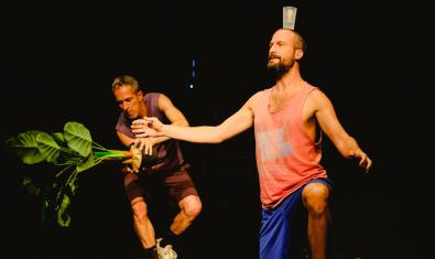 Un dels artistes amb una planta a les mans i un altre amb un got al cap en un moment de la representació