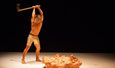 L'artista Quim Girón vestit amb uns pantalons curts i colpejant un tros de fang amb una eina