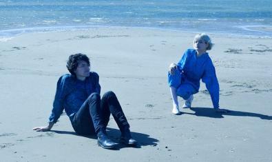 Els dos membres de la formació retratats asseguts sobre la sorra d'una platja