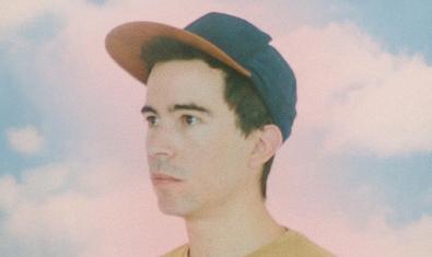 Retrato del artista con una gorra contra un cielo azul con nubes blancas