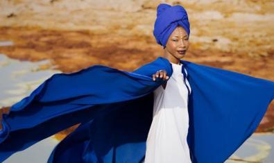 Fatoumata Diawara amb els braços alçats mirant a la càmera, al mig del desert.