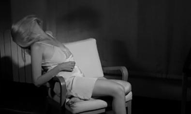 Una dona en combinació asseguda en una butaca amb el cap enrere en una de les peces de vídeo que es projecten al festival