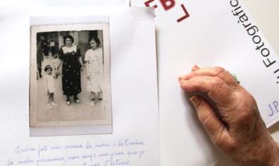 Una mujer mirando una fotografía antigua en blanco y negro donde salen ella, su madre y su hermana
