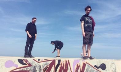 Los tres miembros de la banda retratados subidos sobre un bloque de hormigón lleno de grafiti