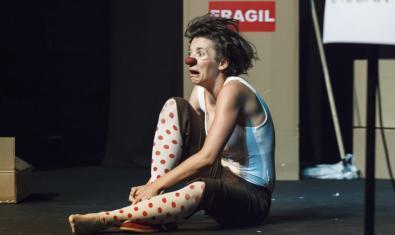 L'artista amb un nas vermell i asseguda al terra en un moment de la representació