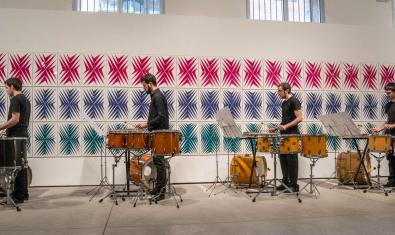 Els quatre membres del grup, en filera, tocant instruments de percussió