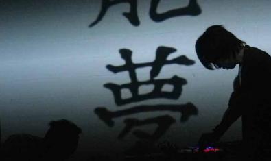 Un dels integrants del duet japonès actuant davant d'una pantalla on es projecten caràcters japonesos