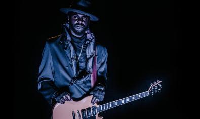 El artista retratado con su guitarra en la oscuridad y contra un fondo negro